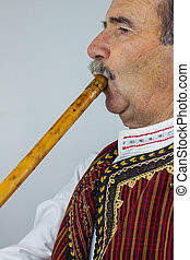 Pipe player in traditional clothing. Woodwind instrument