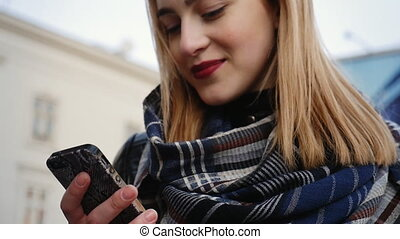 Happy young woman with smartphone in the city, steadicam shot