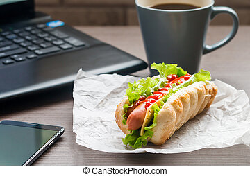 quick lunch of hotdog in the office near the laptop