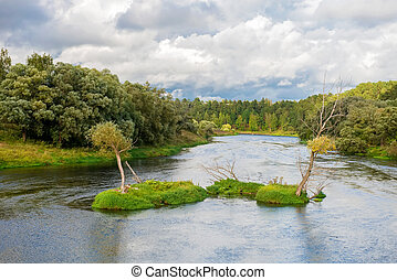 Wide river in green banks overgrown with woods