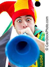 soccer fan blowing vuvuzela - a soccer fan blowing a blue...