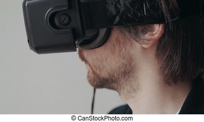 Portrait of Man Using The Virtual Reality Headset And...
