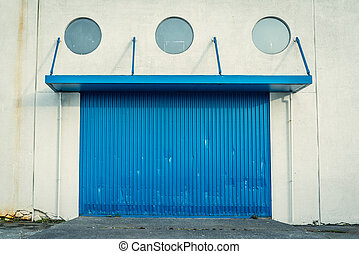 Blue gate on a grungy wall with round windows