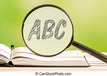 Learning the alphabet abc with a book and a magnifying glass