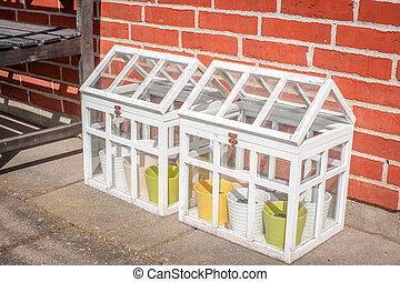 Small outdoors greenhouse in white colors at a terasse