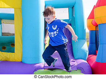 Carefree young boy playing on a bouncy castle exiting a...