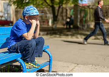 Patient young boy sitting waiting on a blue wooden outdoor...