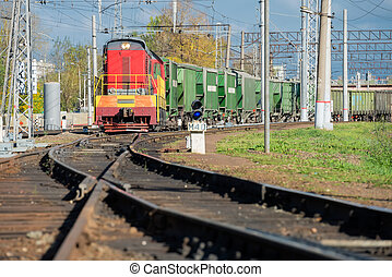 Red locomotive and Green freight cars on the rails