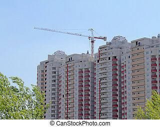 Apartment house under construction with a building crane