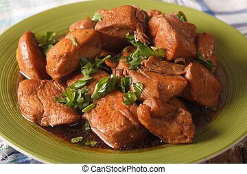 Adobo Chicken with herbs close-up on a plate. horizontal -...