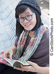 portrait of beautiful asian woman relaxing time reading book on cradle happiness emotion with smiling face