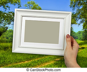 Wooden frame in woman hands on the background Forest...