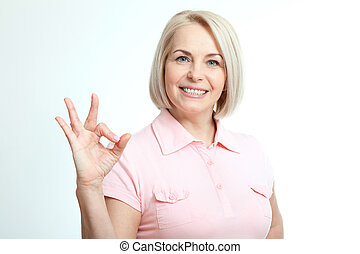 Smilling attractive middle aged woman showing thumbs up,...