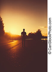 Silhouette of a man standing on the road Weekend photo