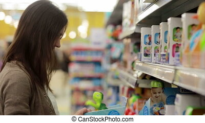 Young woman chooses baby toys in the supermarket - young...