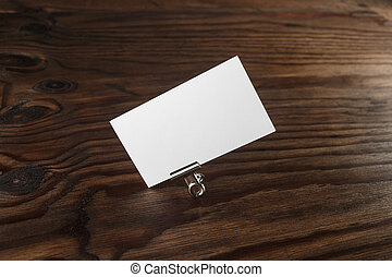 Blank business card and paper clip on dark brown wooden...