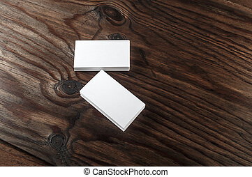Blank white business cards on a dark wooden background...