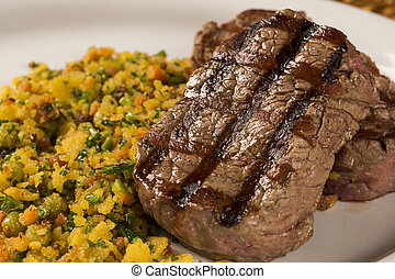 Fillet mignon grilled on plate with crumbs and bacon.