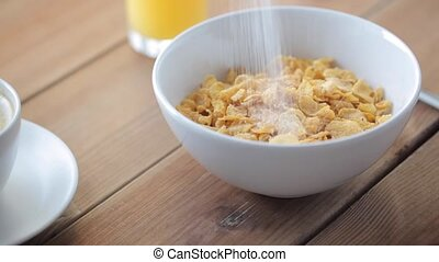sugar pouring to corn flakes on wooden table - breakfast,...