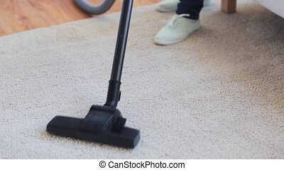 woman with vacuum cleaner cleaning carpet at home - people,...
