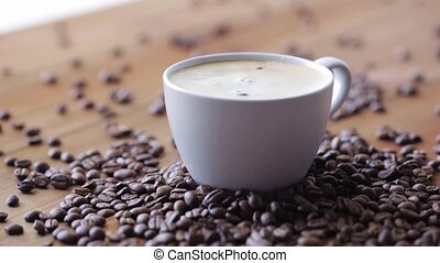 coffee cup and beans on wooden table - caffeine, objects and...