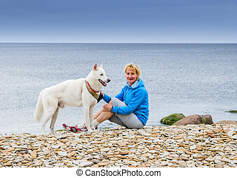 Woman  sits with a dog on the beach