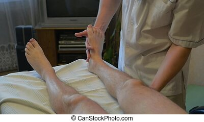 specialist is making a massage to disabled person at home
