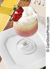 Berry smoothie or milkshake in a tall glass made from a blend of fresh strawberries and raspberries with frozen yoghurt or ice cream for a refreshing summer beverage