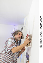 Middle-aged man worker, builder or homeowner plastering a white wall