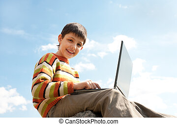 Happy kid studies using a laptop - A happy kid is studying...