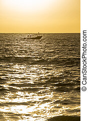 Sunset over ocean water with boat in the horizon