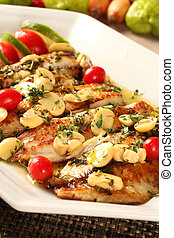 Fish grilled with vegetables in the plate.