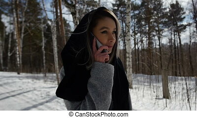 girl talking on the phone walking in the woods