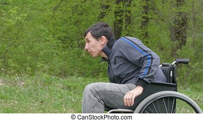 disabled man wheelchair with laptop working on nature green...