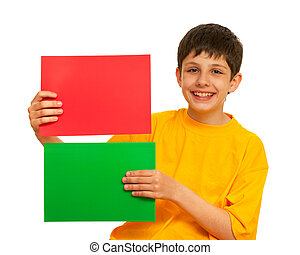 Red or green? - A laughing boy is holding two sheets of...