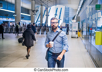 Hipster businessman with coffee cup walking in subway...
