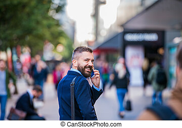 Hipster manager with smart phone walking in the street -...