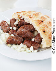 Cevapcici, bosnian minced meat kebab with onion and somun...