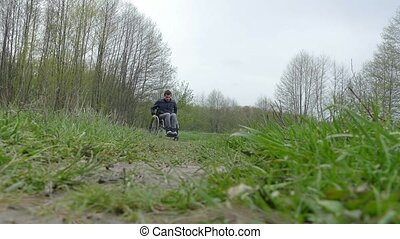 man disabled moving rides wheelchair riding walk on nature...