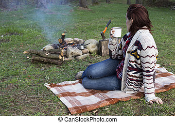 Girl sitting near a campfire at the campsite looking at map...