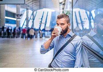 Close up of hipster businessman drinking coffee, subway...