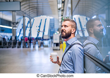 Hipster businessman holding a coffee cup, subway station -...