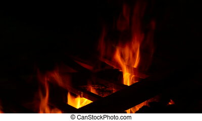 fire with charcoal in a dark room with a grate for cooking -...