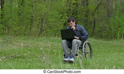 disabled man thinks problems wheelchair with a laptop in a wheelchair working on nature green background