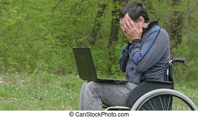 man disabled surprise success victory wheelchair with a laptop in working on nature green background
