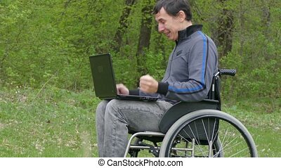 man disabled surprise success victory wheelchair with a laptop in a wheelchair working on nature green background