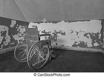 Old wheelchair in corner of room - Old wheelchair facing the...