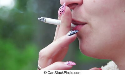 Woman Smokes a Cigarette and Blows Smoke from His Mouth - A...
