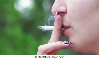 Woman Smokes a Cigarette and Blows Smoke from Her Mouth - A...