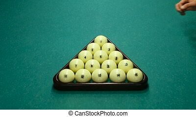 hands men raise the triangle with balls on a pool table